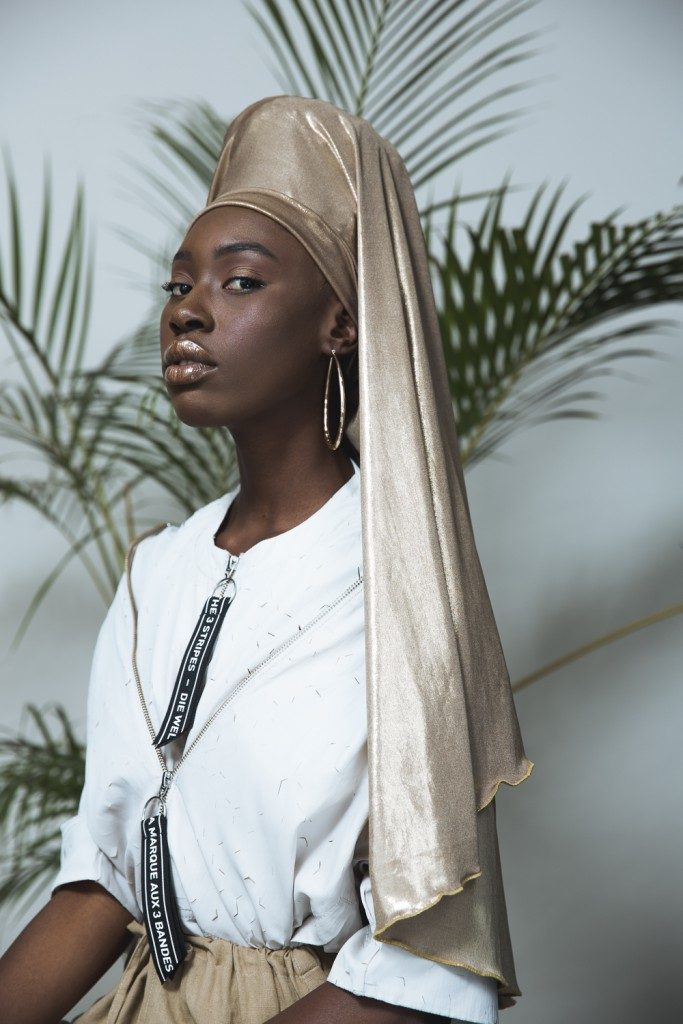 Tatenda WekwaTenzi standing regally in a white dress with tan silk headwrap