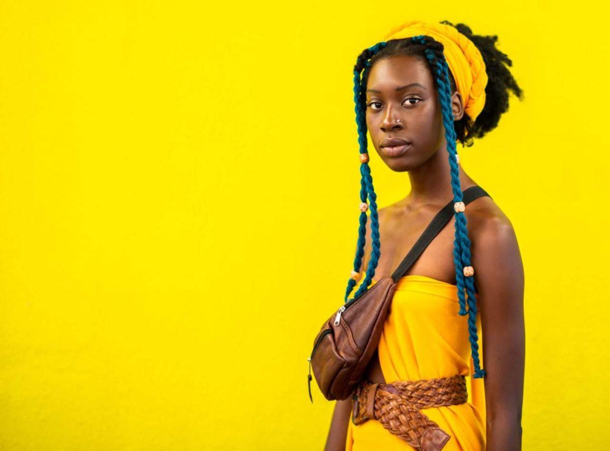 Tatenda WekwaTenzi in yellow dress in front of a yellow background